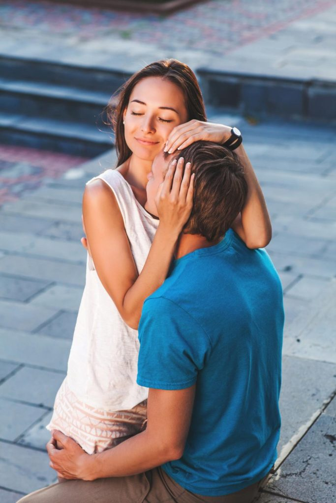 beautiful young brunette girl hugging a loved one guy
