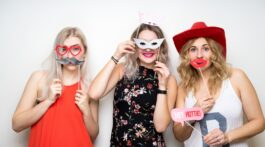 three happy young ladies girls strike a pose on white background photo booth with party props